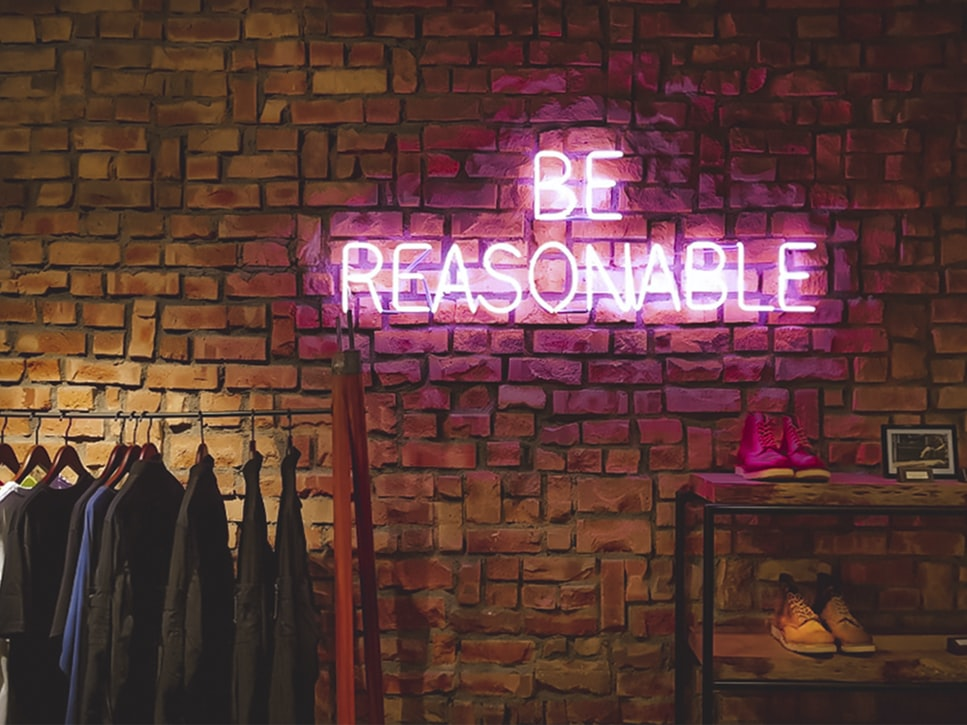 neon 'be reasonable' sign above a clothes rail